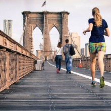 Two people jogging on a bridge